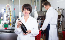 Woman worker displaying wine bottle Royalty Free Stock Image