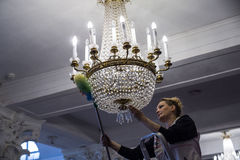 A woman worker looks like the dust from the chandeliers Royalty Free Stock Image