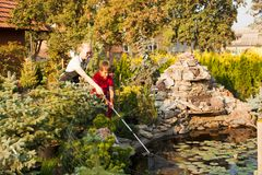 Pupils on the excursion. Woman worker shows the boy a pond, pupils on the excursion. Natural science lesson outdoor Royalty Free Stock Images