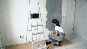 Woman worker using a spatula applying decorative plaster in the apartment or house. Construction, repair and renovation.  stock video