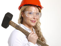Woman working. Working woman with a hardhat and a sledgehammer Royalty Free Stock Photos