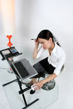 Woman working. An asian woman working at a desk royalty free stock image