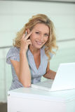 Woman working. Smiling woman in a pretty top working at a white laptop computer royalty free stock photo