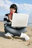 Woman working. Young woman working with computer at the beach Stock Photography