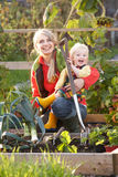 Woman working on allotment with child. Women working on allotment with young child smiling to camera Royalty Free Stock Photos