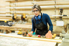 Woman working as carpenter in a workshop. Young Latin female carpenter measuring and marking some wood while woodworking Royalty Free Stock Photos