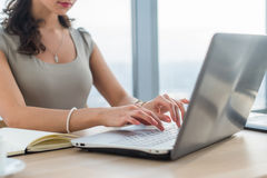 Woman working as copywriter at home. Close-up picture of female hands on pc keyboard in light office. Stock Photos