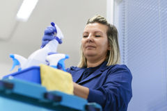 Woman working as professional cleaner in office royalty free stock image