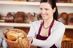 Woman working in a bakery. Offering a customer a basket of assorted bread and rolls with a friendly smile, focus to the woman Stock Photos