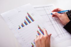 Woman working with bar graphs. Overhead cropped image of female hands working with bar graphs and a spread sheet as she analyses data Stock Images