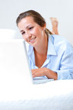 Woman working on bed. Woman with laptop on bed Stock Photos