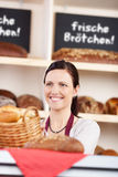 Woman working behind a counter in a bakery. Smiling friendly young woman working behind a counter in a bakery offering a basket of rolls to a customer Stock Photo