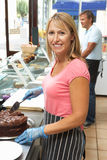 Woman Working Behind Counter In Cafe Slicing Cake Royalty Free Stock Photo