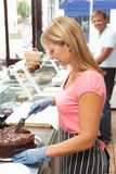 Woman Working Behind Counter In Cafe Slicing Cake Royalty Free Stock Photography