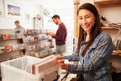 Woman working behind the counter at a record shop, portrait Royalty Free Stock Images