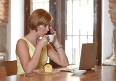 Woman working busy at coffee shop with laptop computer talking on mobile phone Royalty Free Stock Photo
