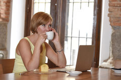 Woman working busy at coffee shop with laptop computer talking on mobile phone Stock Photos