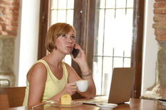 Woman working busy at coffee shop with laptop computer talking on mobile phone Stock Image