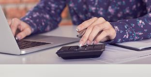 Woman working with calculator, business documents and laptop computer close-up. royalty free stock image