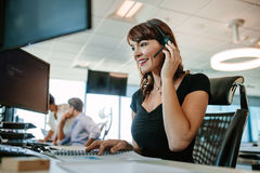 Woman working in call center. Call center business women talking on headset. Caucasian female in customer service position talking on the phone royalty free stock photos