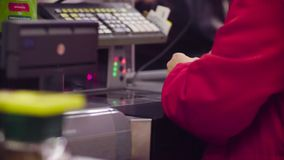 Woman working on cash register in the store. Close up check out counter. Rear view of hands of woman working on cash register in the supermarket stock video footage