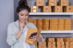 Woman working and checking product order with smartphone at home stock images