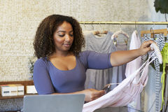 Woman working in clothes shop holding a dress, close up Stock Photo