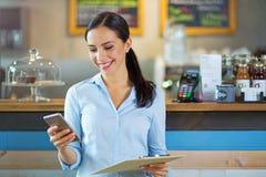 Woman working in coffee shop Stock Image