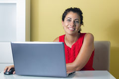 Woman Working on Computer. Woman sitting at home, working on a computer Royalty Free Stock Photography