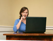 Woman Working on Computer. A woman is working on a computer and chewing on her pen Royalty Free Stock Photos