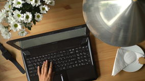A woman working at a computer with coffee and bouquet of flowers on the table. Dolly shot stock video