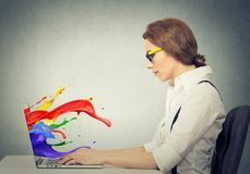 Woman working on computer colorful splashes coming out of screen. Side view profile attractive happy young business woman working on laptop computer colorful Stock Photos