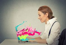 Woman working on computer colorful splashes coming out of screen Stock Photography