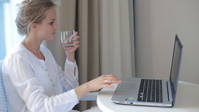 Woman working on computer and drink. Caucasian woman working on computer laptop and drink water stock footage