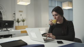 A woman working at the computer and drinking orange juice stock video footage