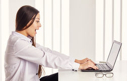 Woman working on computer. Girl excited what she see on laptop screen browsing internet. Face expression emotion Royalty Free Stock Photos