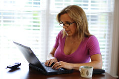 Woman working on computer at home based business. Woman wearing glasses working on computer at home based business Stock Image