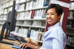 Woman working on computer in library Royalty Free Stock Photo