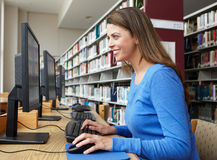 Woman working on computer in library Stock Images