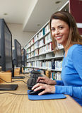 Woman working on computer in library Stock Image