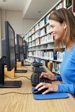 Woman working on computer in library Royalty Free Stock Photos