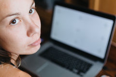 Woman working on computer and looking at the camera Royalty Free Stock Images