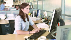 Woman Working At Computer In Modern Office. Woman sitting at desk working on computer is joined by male colleague who shows her information on digital tablet stock video