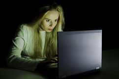 Woman working on a computer by night horizontal Stock Photos