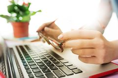 Woman working on computer in office and holding glasses. Woman and fruit diet while working on computer in office. Female hands on keyboard. Side view on woman Stock Images