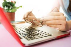 Woman working on computer in office and holding glasses. Woman and fruit diet while working on computer in office. Female hands on keyboard. Side view on woman Royalty Free Stock Photo
