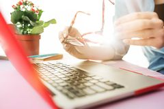 Woman working on computer in office and holding glasses. Woman and fruit diet while working on computer in office. Female hands on keyboard. Side view on woman Royalty Free Stock Images