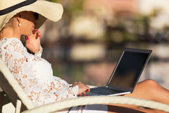Woman working with computer outdoors Stock Photo