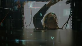 Woman working on a computer server with moving data security messages. Animation of a Caucasian woman working on computer server seen close up from inside the stock footage