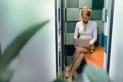 Woman working with computer in silent booth Stock Images